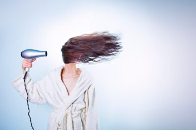 Silver hairdryer electrical appliance blowing a ladies hair across her face whilst she wears a bathrobe