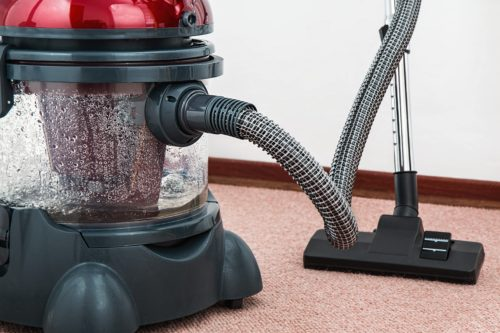Red vacuum cleaner for cleaning carpets