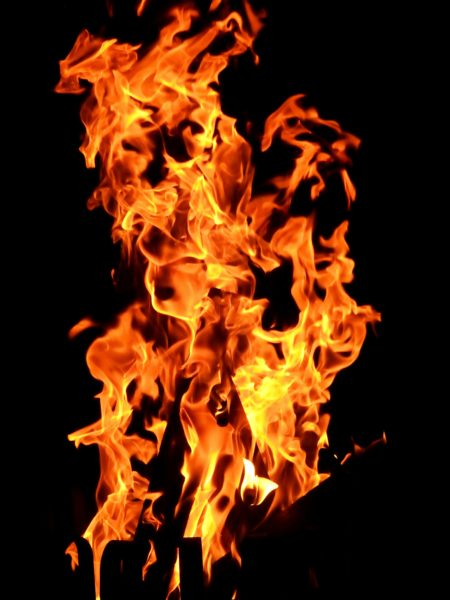 Orange fire burning on a black background to suggest electrical fire