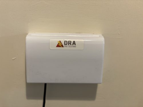 Double socket protected with a latched socket cover, with a DRA PAT Testing sticker on